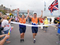 Charlotte Nichols and Stuart Bates finishing their marathon at Weymouth Beach (Andrew Matthews/PA)