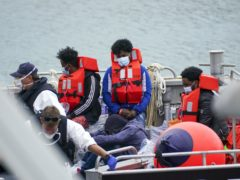 A group of people thought to be migrants are brought in to Dove (PA)