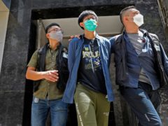 A student of Hong Kong University, centre, is escorted by police officers after a home search in Hong Kong (Vincent Yu/AP)