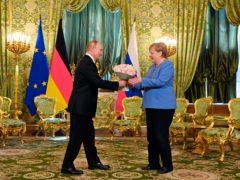 Russian President Vladimir Putin presents flowers to German Chancellor Angela Merkel during their meeting in the Kremlin in Moscow (Sputnik, Kremlin Pool Photo via AP)