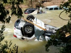 Vehicles come to rest in a stream Sunday, Aug. 22, 2021, in Waverly, Tenn. Heavy rains caused flooding Saturday in Middle Tennessee and have resulted in multiple deaths as homes and rural roads were washed away. (AP Photo/Mark Humphrey)