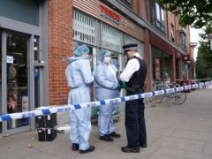 Police officers in forensic suits speak to a colleague outside Tesco Express on Fulham Palace Road (Jonathan Brady/PA)