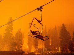 The Caldor Fire burns as a chairlift sits motionless at the Sierra-at-Tahoe ski resort (Noah Berger/AP)
