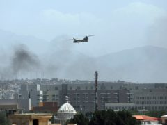 A U.S. Chinook helicopter flies over the city of Kabul, Afghanistan, Sunday, Aug. 15, 2021. Taliban fighters entered the outskirts of the Afghan capital on Sunday, further tightening their grip on the country as panicked workers fled government offices and helicopters landed at the U.S. Embassy. (AP Photo/Rahmat Gul)