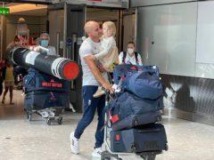 Canoeist Liam Heath is reunited with his three-year-old daughter Sarah at Heathrow Airport (Elmira Tanatarova/PA)
