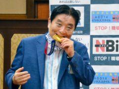 Nagoya mayor Takashi Kawamura, left, bites the Olympic gold medal of Miu Goto, right, of Japan softball team who won the event at the 2020 Summer Olympics (Kyodo News via AP)