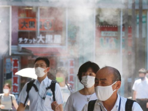 People wearing face masks to protect against the spread of the coronavirus walk under a water mist in Tokyo (AP)