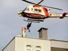 A Coast Guard helicopter rescues a man stranded on a rooftop in Bozkurt, Turkey (IHA via AP)