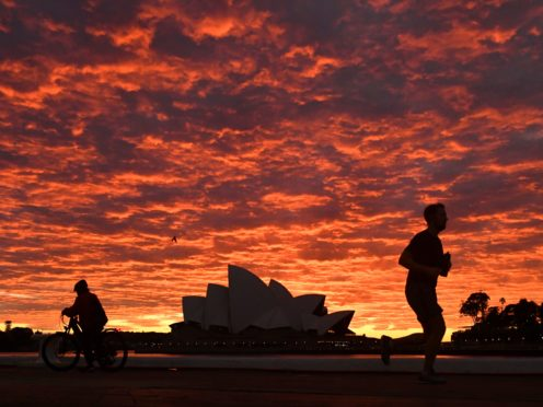 A jogger runs past the Sydney Opera House at dawn (Mick Tsikas/AAP Image via AP)