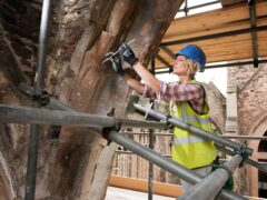 A building conservator works on the Church of St Peter in Bristol (James O. Davies/Historic England/PA)