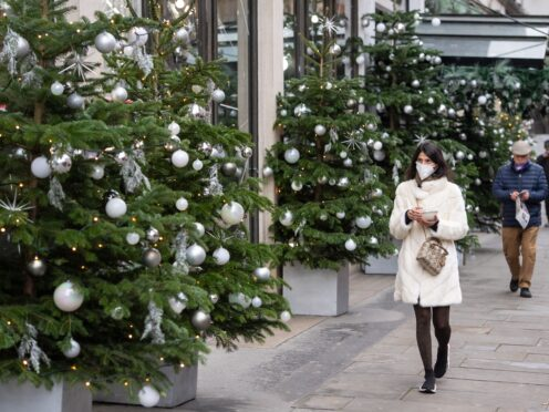 A woman wearing a face mask passes a display of Christmas trees (Dominic Lipinski/PA)