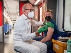 Christian Gravert, left, chief medical officer of the Deutsche Bahn, vaccinates a man with the Johnson & Johnson, or Janssen, vaccine in a special train of Berlin's public transport S-Bahn, in which vaccination against Covid-19 are offered (Christophe Gateau/AP)