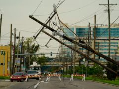 Vehicles are diverted around utility poles damaged by the effects of Hurricane Ida in New Orleans (Eric Gay/AP)