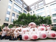 Protesters wearing inflatable breasts stand outside Facebook's headquarters in central London, to complain about the social media giant's images algorithm (PA)