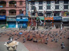 Pigeons fly in a deserted market area in Srinagar, Indian controlled Kashmir (Mukhtar Khan/AP)
