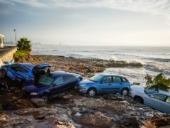 Wrecked cars stuck in the shore of the seaside town of Alcanar, in northeastern Spain, Thursday, Sept. 2, 2021. A downpour Wednesday created flash floods that swept cars down streets in the Catalan town of Alcanar. Most of mainland Spain is under alert for heavy rains. (AP Photo/Joan Mateu Parra)