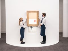 Art handlers at Sotheby's auction house with Banksy's Love Is In The Bin, which self-shredded immediately after it was sold at auction (Dominic Lipinski/PA)