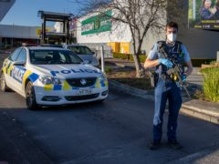 Armed police stand outside the supermarket in Auckland (Brett Phibbs/AP)