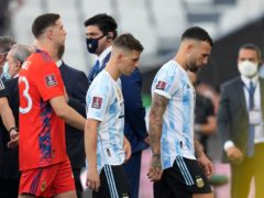 Argentina's Giovani Lo Celso (centre) walks off the pitch with Nicolas Otamendi (right) and goalkeeper Emiliano Martinez (Andre Penner/AP).