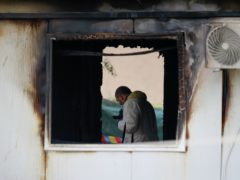 A forensic officer works at the site after a fire at a makeshift hospital in North Macedonia (AP Photo/Visar Kryeziu)