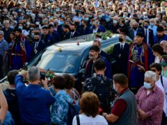 Men in traditional dress of the island of Crete escort a hearse, ahead of the burial of Greek composer Mikis Theodorakis in Crete (AP Photo/Michael Varaklas)