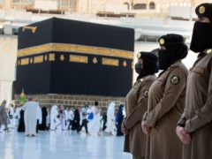 Saudi police women, who were recently deployed to the service, from right to left, Samar, Alaa, and Bashair, stand alert in front of the Kaaba, the cubic building at the Grand Mosque, during the annual hajj pilgrimage (Amr Nabil/AP)