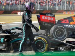Lewis Hamilton walks away from his Mercedes after colliding with Max Verstappen (Luca Bruno/AP)