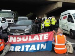 Police speaking to one another as protesters block an M25 junction on Monday (Insulate Britain/PA)