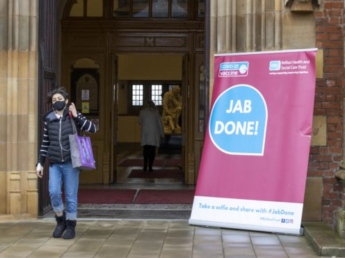 """A woman walks past a Covid-19 """"Jab Done!"""" sign at Queen's University, Belfast (Liam McBurney/PA)"""