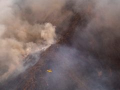 A seaplane flies over a wildfire in southern Spain (Pedro Armestre/AP)