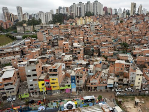 Workers paint the facades of residences in the Paraisopolis favela, as part of the community's centennial celebration (Andre Penner/AP)