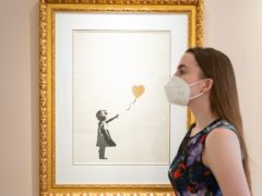 Rare works from subversive street artist Banksy – including Girl With Balloon – Colour AP (gold) – went on display ahead of an auction later this month (Dominic Lipinski/PA)