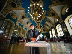 A man casts his ballot at a polling station at the Kazansky railway station during the Parliamentary elections in Moscow, Russia (Alexander Zemlianichenko/AP)