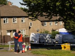 The father of some of the victims leaves flowers at the scene in Chandos Crescent, Killamarsh, near Sheffield (PA)