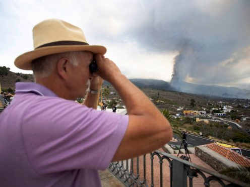 A man looks out towards the eruption of a volcano near El Paso on the island of La Palma in the Canaries, Spain, Monday, Sept. 20, 2021. Lava continues to flow slowly from a volcano that erupted in Spain's Canary Islands off northwest Africa. Officials say they are not expecting any other eruption and no lives are currently in danger. (AP Photo/Gerardo Ojeda)