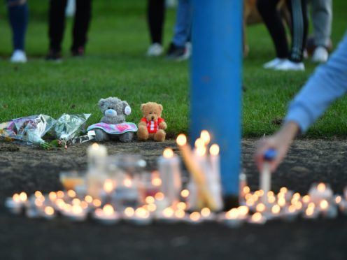 Flowers, soft toys and candles are seen at a vigil at the scene (Anthony Delvin/PA)