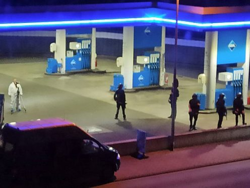 Police officers secure a petrol station in Idar-Oberstein, Germany after a man was arrested on suspicion of murder (Christian Schulz/Foto Hosser/dpa via AP)