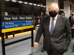 Boris Johnson prepares to board a train from Penn Station in New York to Washington DC (Stefan Rousseau/PA)