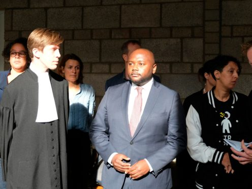 Mpanzu Bamenga with his legal team and rights activists outside a courtroom at The Hague District court (AP Photo/Mike Corder)