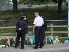 Police officers stand by floral tributes at Cator Park in Kidbrooke (Ian West/PA)
