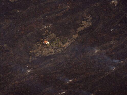 Lava from a volcano eruption surrounds a house on the island of La Palma (Emilio Morenatti/AP)