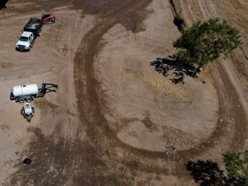 Crews clear an area which was occupied by migrants in Texas (Julio Cortez/AP)