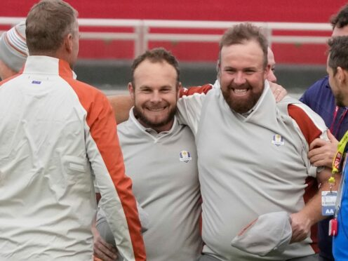 Shane Lowry and Tyrrell Hatton celebrate on the 18th hole after winning their four-ball match on day two of the Ryder Cup (Charlie Neibergall/AP)
