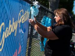 A woman places a decoration near a poster after attending the funeral home viewing of Gabby Petito at Moloney's Funeral Home in Holbrook, New York (Eduardo Munoz Alvarez/AP)