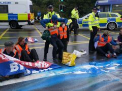 Police officers detain protesters from Insulate Britain occupying a roundabout leading from the M25 motorway to Heathrow Airport in London (Steve Parsons/PA)