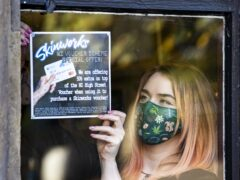 Tattoo apprentice Amy Lawless posts an ad in the window of Belfast City Skinworks, Tattoo and Piercing Studio. The studio is offering 50% extra on top of the Northern Ireland High Street voucher scheme, when using it to purchase a Skinworks voucher (Liam McBurney/PA)