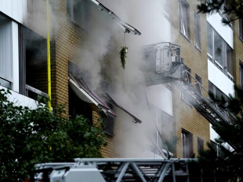 Smoke billows from an apartment building after an explosion in Annedal (TT via AP)