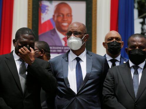 Haiti's designated prime minister Ariel Henry, centre, and interim prime minister Claude Joseph, right, pose for a group photo with other authorities in front of a portrait of murdered Haitian President Jovenel Moise (Joseph Odelyn/AP)