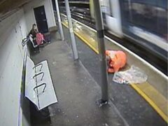 A rail worker removing rubbish from train tracks narrowly avoided being hit by a train, an investigation has found (RAIB/PA)
