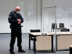 A judicial officer in the court room in Itzehoe, Germany, looks at his watch prior to the trial (Markus Schreiber, Pool/AP)